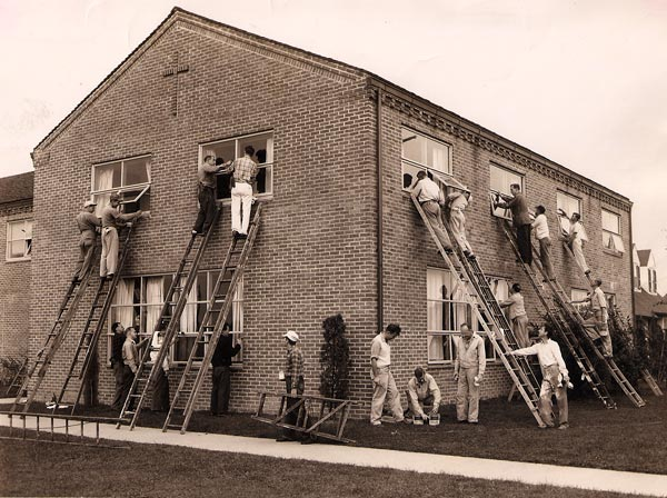 Volunteers working to install windows of the Parish House.